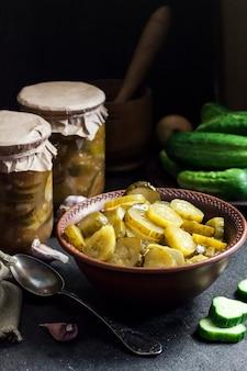 Eingelegter gurkensalat in einer schüssel und gläser auf schwarzem hintergrund