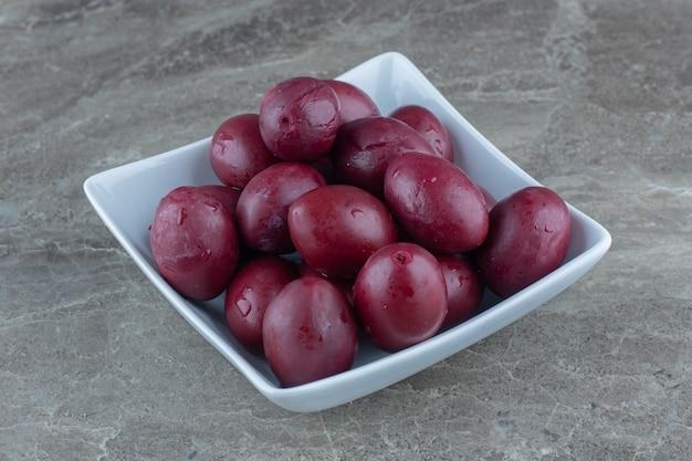 Eingelegter haufen oliven in weißer keramikschale