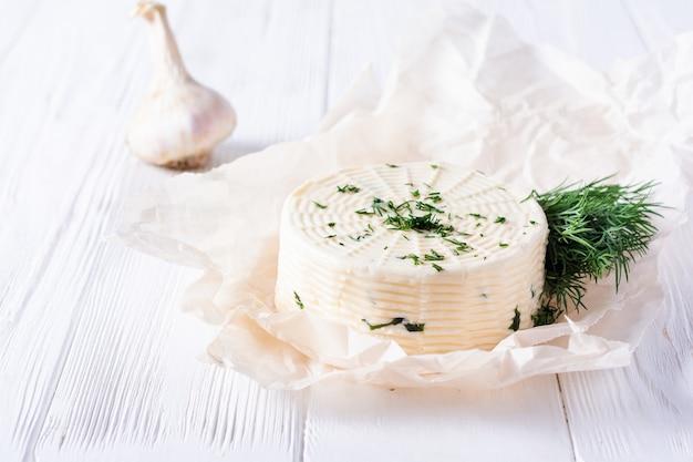 Eingelegter käse mit dill, gewürzen und knoblauch auf einem weißen holztisch. selektiver fokus