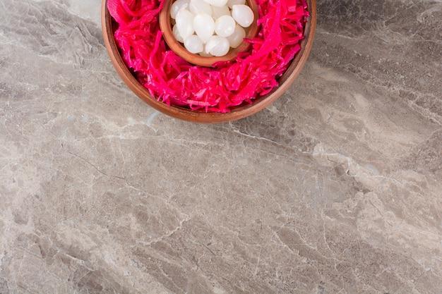 Eingelegter rotkohl mit knoblauchzehen auf steintisch.