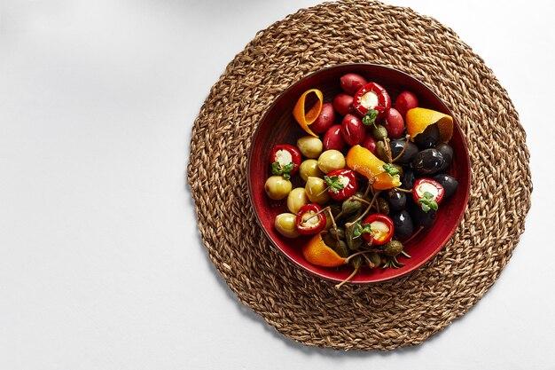 Eingelegtes gemüse in einem teller, oliven, oliven, gefüllte paprika, radieschen. verschiedene gemüse, gemüse mit gewürzen in öl nahaufnahme auf weißem hintergrund, ansicht von oben, exemplar