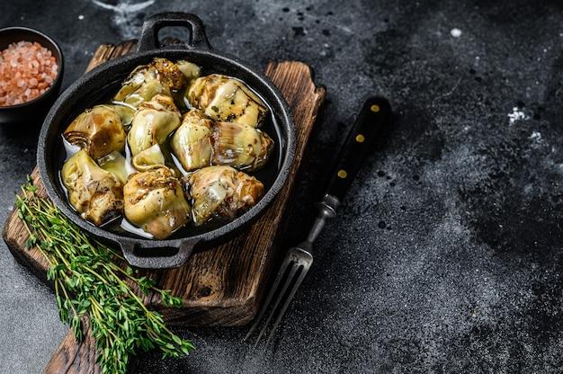 Eingemachte artischocken in olivenöl auf einem rustikalen küchentisch aus holz. schwarzer hintergrund. ansicht von oben. platz kopieren.