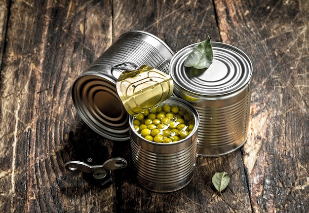 Eingemachte grüne erbsen in einer blechdose mit öffner. auf einem hölzernen hintergrund.