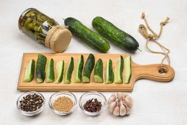 Eingemachte gurken, gehackte gurken auf schneidebrett, grüne petersilie, knoblauch und gewürze. hausgemachte fermentationsprodukte. gesunde winterernährung. weiße oberfläche. draufsicht.