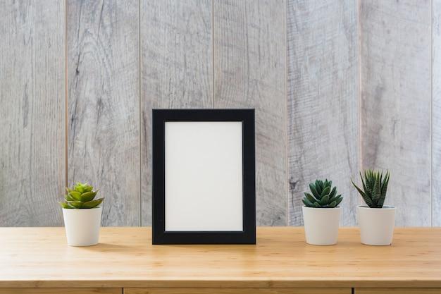 Eingemachte kaktuspflanze und weißer bilderrahmen mit schwarzer grenze auf tabelle