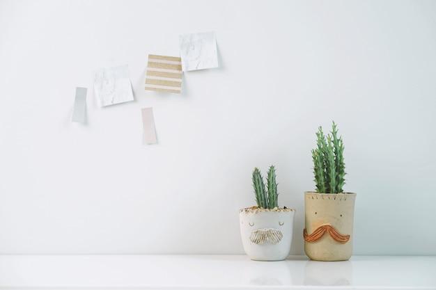 Eingemachte kaktuszimmerpflanzen mit klebriger anmerkung über weiße wand.
