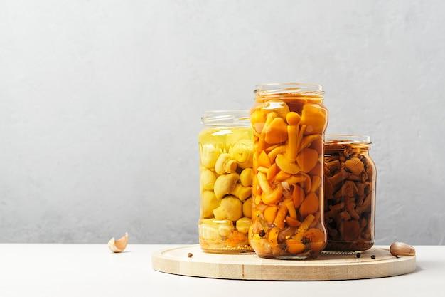 Eingemachte pilze in dosen auf einem konkreten hintergrund mit kopien des raumes.