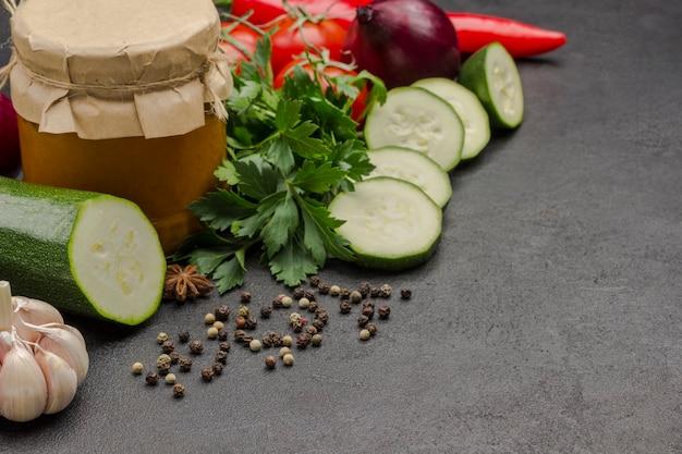 Eingemachter kürbis im glas verteilt. rohes gemüse und gewürze: karotten knoblauch, zwiebeln tomaten, pfefferkorn. gesunde winterernährung. fermentationsprodukte. . speicherplatz kopieren