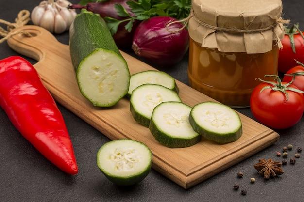 Eingemachter kürbis im glas verteilt. rohes gemüse und gewürze: karotten knoblauch, zwiebeln tomaten, sternanis, chili pfefferkorn, petersilie. gesunde winterernährung. fermentationsprodukte.