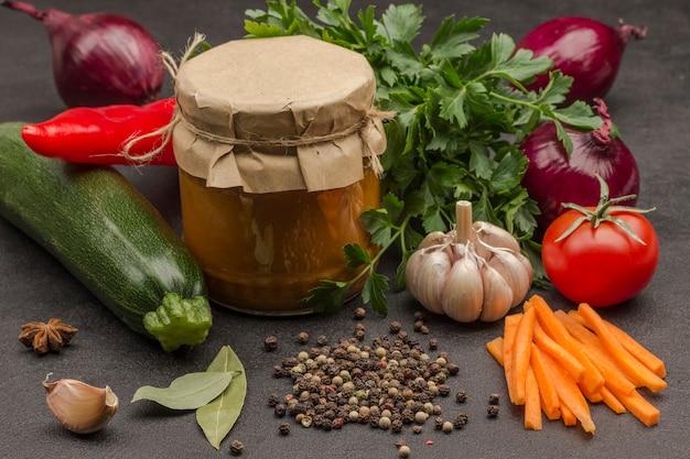 Eingemachter kürbisaufstrich im glas rohes gemüse und gewürze karotten knoblauch zwiebeln tomaten sternanis chili pfefferkorn petersilie