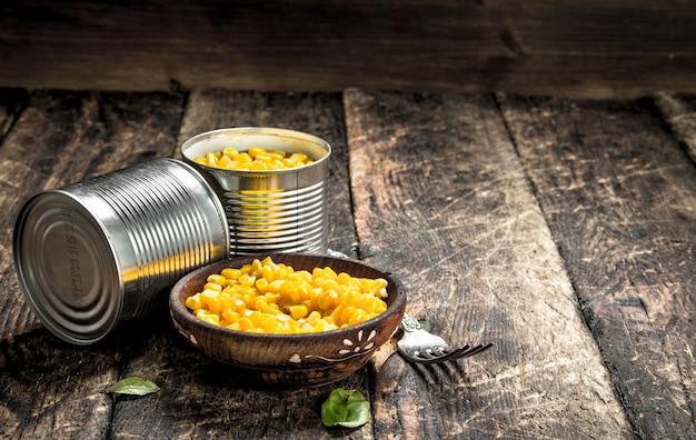Eingemachter mais in einer blechdose mit gabel auf holztisch.