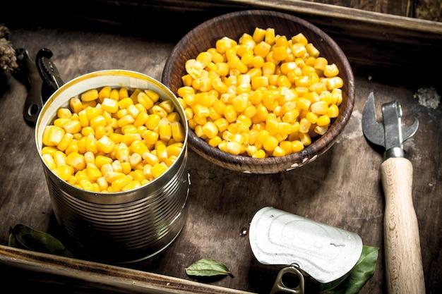 Eingemachter mais in einer blechdose mit öffner. auf einem hölzernen hintergrund.