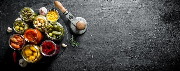 Eingemachtes essen in gläsern auf einem steinbrett mit knoblauchzehen. auf schwarzem rustikalem hintergrund