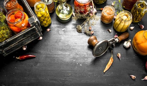 Eingemachtes gemüse und pilze in einer schachtel mit seemann. auf der schwarzen tafel.