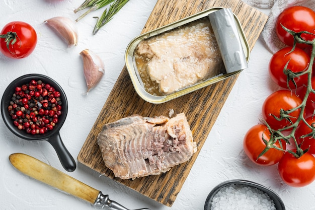 Eingemachtes wild pink salmon set, auf holzschneidebrett, auf weißem tisch mit kräutern und zutaten, draufsicht flach gelegt
