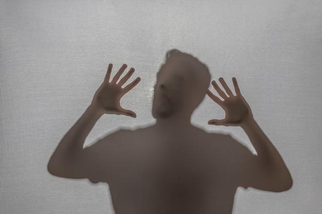 Eingeschlossener mann, der hinter stoff schreit