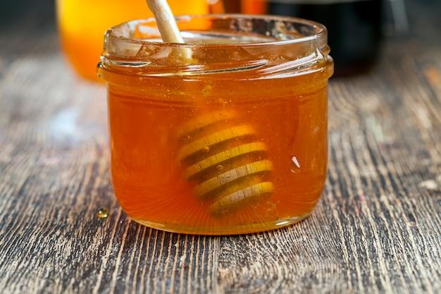 Eingetaucht in honig, der speziell aus holz hergestellt wurde, hausgemachter grober löffel, süßer bienenhonig und holzlöffel, mit dem sie honig übertragen und gießen können, ohne zu tropfen und zu verteilen