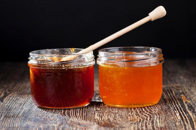 Eingetaucht in honig speziell aus holz, hausgemachter grober löffel, süßer bienenhonig und ein holzlöffel, mit dem sie honig ohne tropfen und ausbreiten übertragen und gießen können