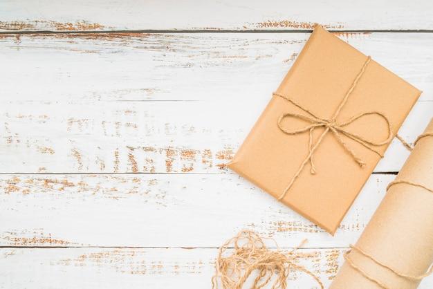 Eingewickelte braune geschenkpapiergeschenkbox auf hölzernem hintergrund