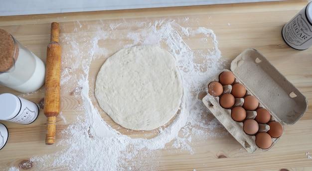 Eingewickelte eier, teig, mehl und nudelholz in der küchentheke