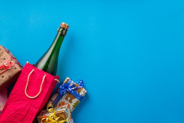 Eingewickelte geschenk- und champagnerflasche über blauem hintergrund