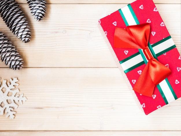Eingewickelte geschenkbox auf dem holzbrett. weihnachts- und neujahrskonzept