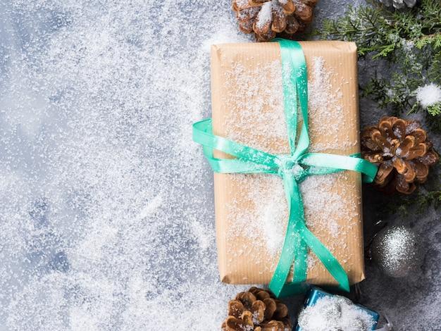Eingewickelte geschenkbox des weihnachtsneuen jahres mit band und schnee. tannenzapfen und dekorationen. winter festlichen hintergrund