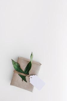 Eingewickelte geschenkbox mit tag und blättern auf weißem hintergrund