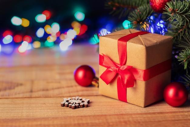 Eingewickelte geschenkbox unter weihnachtsbaum auf holztisch gegen unscharfe lichterketten, kopierraum. neujahrs- und weihnachtsferien
