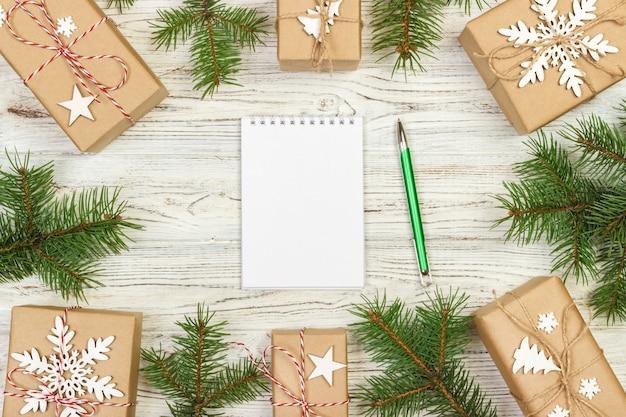 Eingewickelte geschenkboxen mit handgeschriebenen anmerkungen nähern sich fichtenzweig auf weißer hölzerner, draufsicht, geheimem sankt-weihnachtsspiel