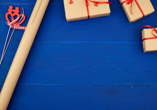 Eingewickelte geschenke in braunes bastelpapier und gebunden mit einem roten band, einer papierrolle