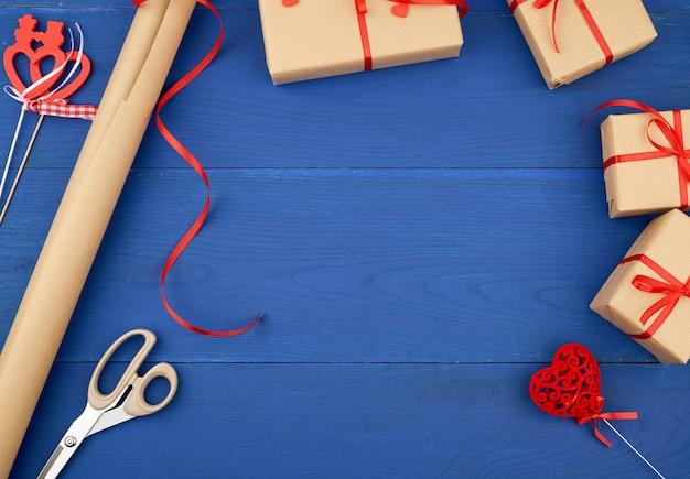 Eingewickelte geschenke in braunes bastelpapier und gebunden mit einem roten band
