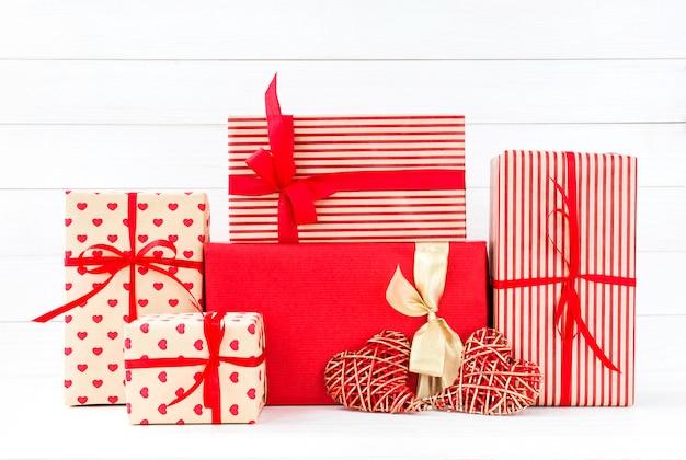 Eingewickelte geschenkkästen und zwei rote herzen auf weißem hölzernem hintergrund. platz kopieren