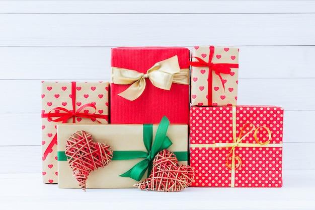 Eingewickelte geschenkkästen und zwei rote herzen auf weißem hölzernem hintergrund.