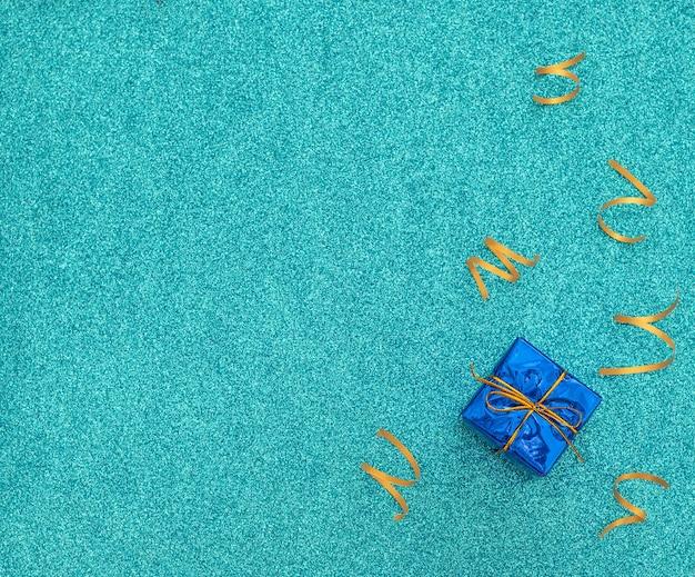 Eingewickelte klassische blaue geschenkbox mit goldenem band auf feierblau mit hellen party-luftschlangen.