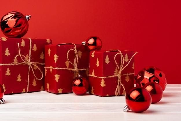 Eingewickelte weihnachtsgeschenkboxen gegen roten hintergrund