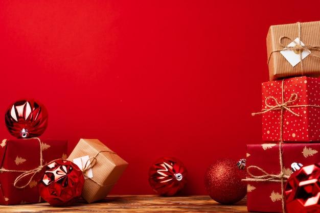 Eingewickelte weihnachtsgeschenkboxen gegen vorderansicht des roten hintergrunds