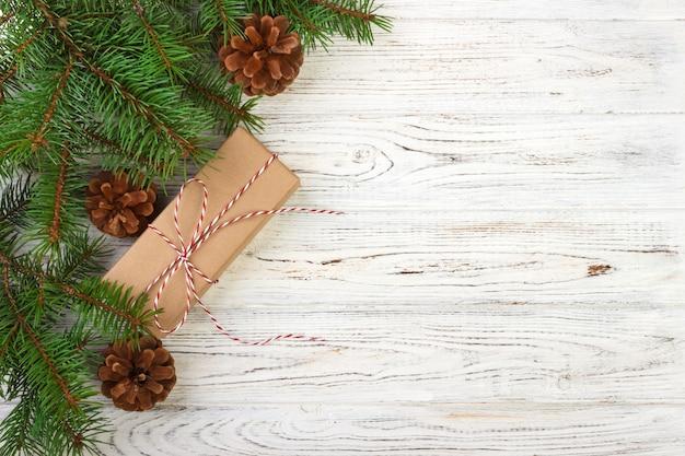 Eingewickelte weihnachtsgeschenke auf dunklem rustikalem hölzernem hintergrund mit kiefernkegeln und tannenzweigen. mit textfreiraum