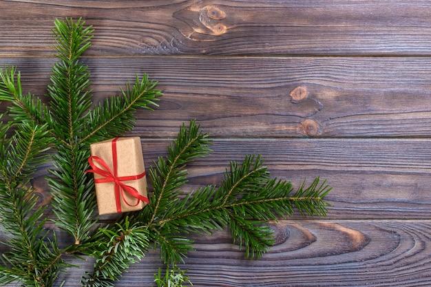 Eingewickelte weihnachtsgeschenke auf dunklen rustikalen holztisch-tannenzweigen,