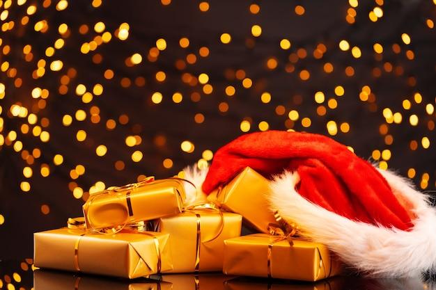 Eingewickelte weihnachtsgeschenke auf goldenem lichtbokeh