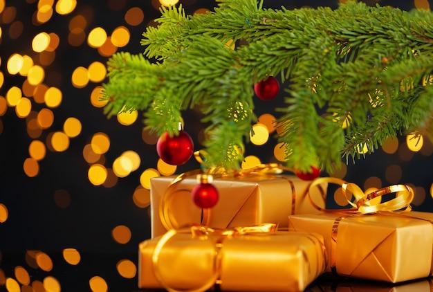 Eingewickelte weihnachtsgeschenke auf goldenem lichtbokehhintergrund