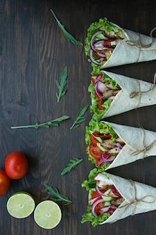 Eingewickelter burrito mit hühner- und gemüsenahaufnahme auf einem holztisch.