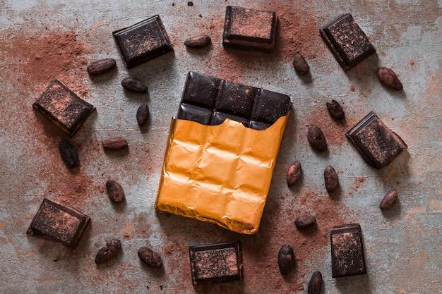 Eingewickelter schokoriegel und kakaobohnen auf rustikalem hintergrund