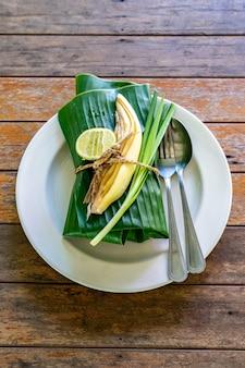 Eingewickelter thailändischer nahrungsmittelsatzabdeckung durch servierfertiges bananenblatt. im inneren des bananenblattes befindet sich padthai, die traditionelle gebratene nudel thailands mit garnelen.
