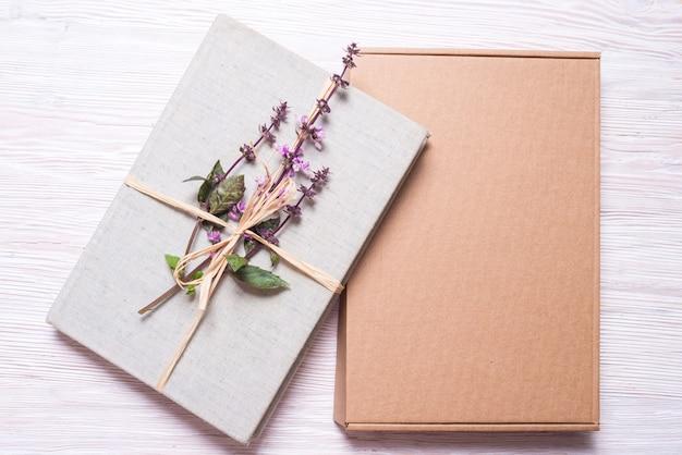 Eingewickeltes buch mit blumen in der geschenkbox aus pappe