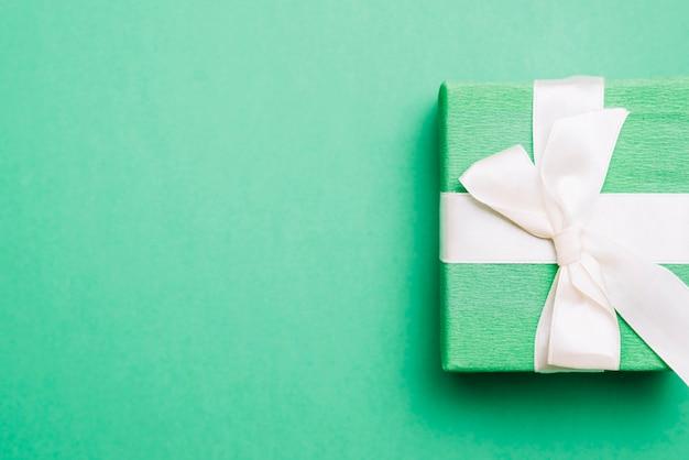 Eingewickeltes geburtstagsgeschenk mit weißem bandbogen auf grünem hintergrund