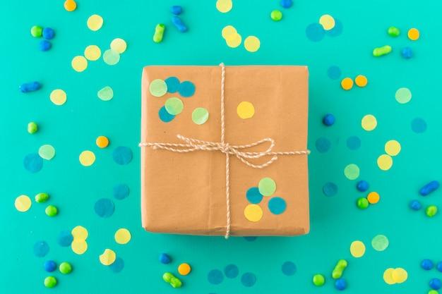 Eingewickeltes geburtstagsgeschenk umgeben mit süßigkeiten und konfetti auf grüner oberfläche
