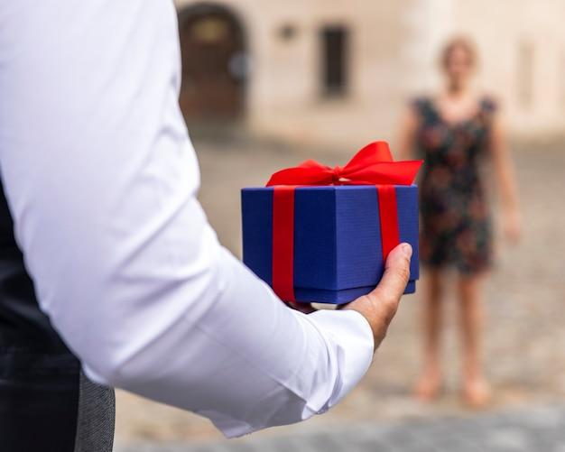 Eingewickeltes geschenk der vorderansicht gehalten vom mann
