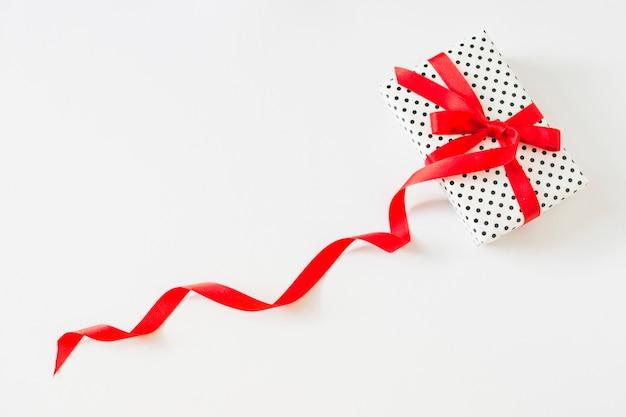 Eingewickeltes geschenk gebunden mit rotem band auf weißem hintergrund