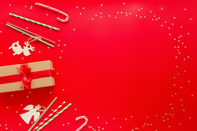 Eingewickeltes geschenk, hölzerne spielwaren, die auf rotem hintergrund liegen